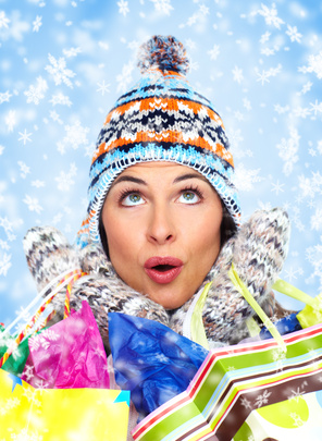 Beautiful christmas girl with shopping bags. Over winter background.