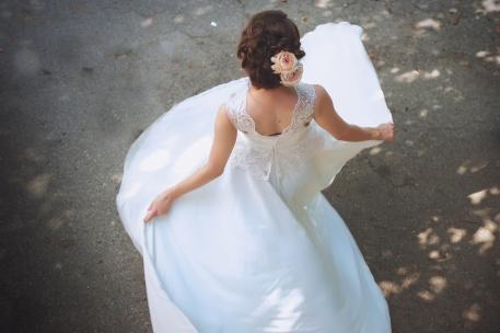 Beautiful bride standing back in her wedding dresss