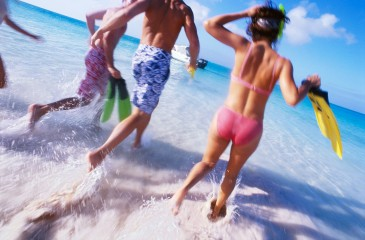 Group of Friends Running Into the Water Wearing Snorkeling Gear --- Image by © Royalty-Free/Corbis